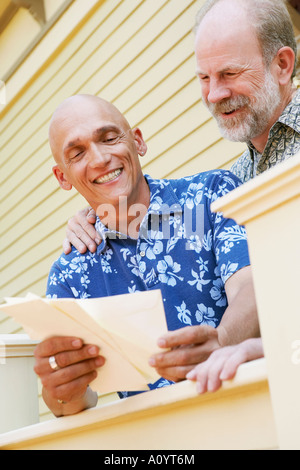 Gay couple reading mail - Stock Image