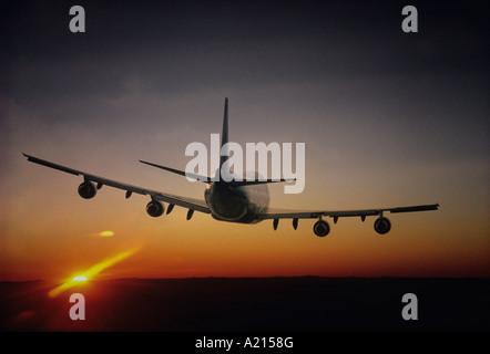 Plane Flying, sun setting on horizon, back view - Stock Image