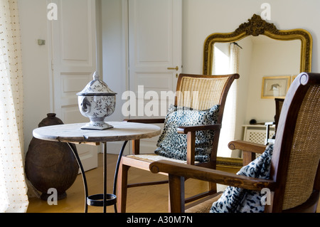 Two wicker chairs at a side table with a gilt framed mirror - Stock-Bilder