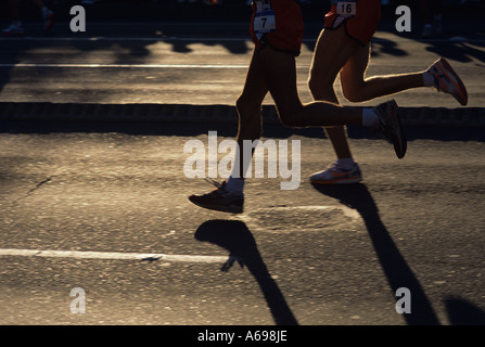 Seattle marathon early morning downtown streets with sunlight highlighting two runners Seattle Washington USA - Stock Image