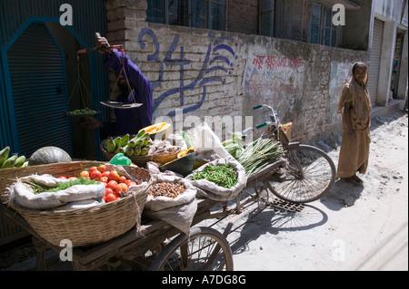 A vegetable vender goes door to door selling vegetables in Dhaka Bangladesh - Stock Image