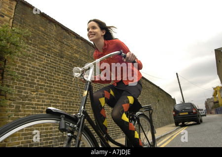 A girl speeding on an old-model cycle on a road with a brick wall beside and a car parked in the background. - Stock-Bilder