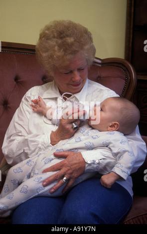 grandmother bottlefeeding baby - Stock Image