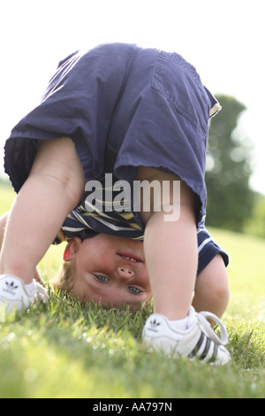 One year old boy upside down looking through legs - Stock Image