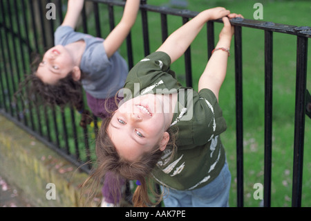 Two six year old girls playing on metal railings, London, UK. - Stock Image