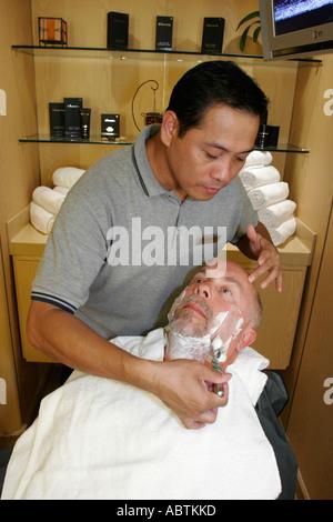 Puerto Rico Atlantic Ocean Holland America Line ms Noordam Greenhouse Salon Asian male shaves White man cream - Stock Image