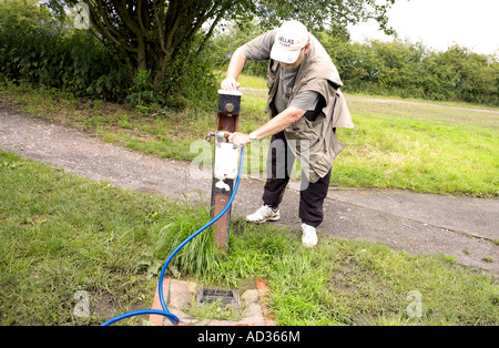 Narrowboat steerer taking on water at a water point on the Ashby Canal - Stock Image