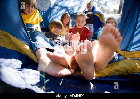 A woman and a group of children piled up in a tent - Stock-Bilder