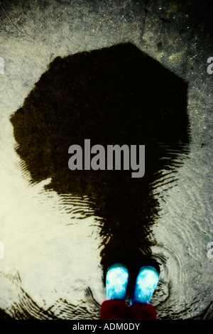 Reflection in a puddle, child with wellington boots - Stock Image