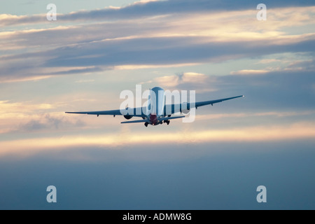 Commercial airplane during flight in the clouds - Stock Image