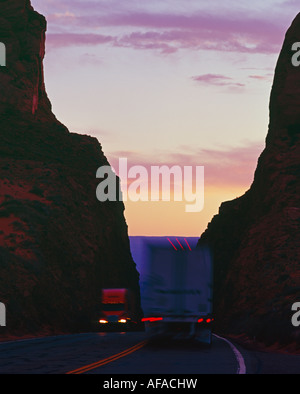 Truckers pass at twilight on a desert highway in northern Arizona - Stock Image