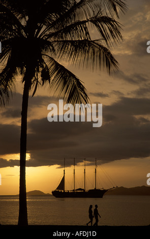 Venezuela Puerta la Cruz Caribbean Sea shore couple sunset masted sailing ship SV Fantome - Stock Image