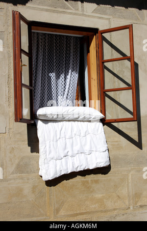 Bedding is aired at a window. Photo by Willy Matheisl - Stock Image