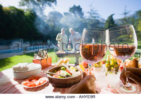 Men grilling food at family barbecue in summer garden focus on food and wine on table in foreground - Stock Image