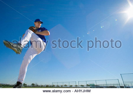 Baseball pitcher, in blue uniform, preparing to throw ball during competitive game, side view lens flare, surface - Stock Image