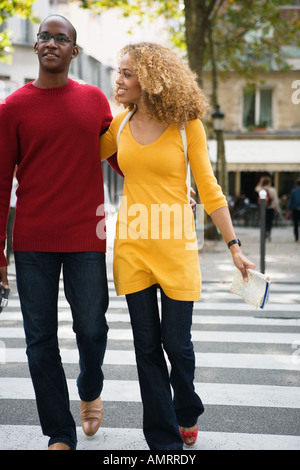 African couple walking across street - Stock-Bilder