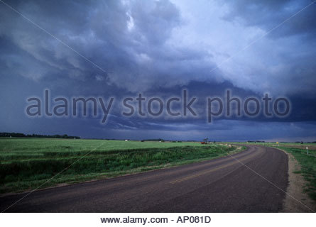 Stormy Sky looms over curving road through wheat field in central   Kansas USA road leading off into the distance - Stock Image