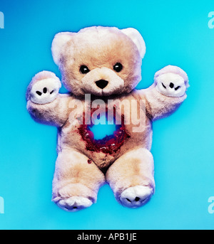Teddy bear with a gun shot wound - Stock Image