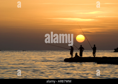 Silhouette of three men fishing by sunset - Stock Image