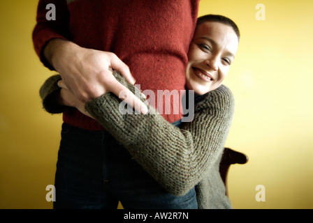 Young woman with short hair hugging her couple and smiling - Stock-Bilder