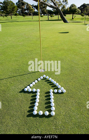An arrow pointing to a hole on a golf green - Stock Image