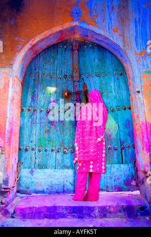 Woman in Old Delhi by a colorful door, India - Stock Image