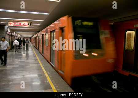 Speeding orange-coloured underground metro train in Mexico City. Showing passengers on the platform and the SALIDA - Stock Image
