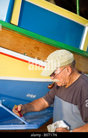 Man repainting a Luzzu_A Traditional Maltese foreign fishing boats - Stock-Bilder