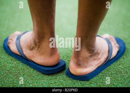 Back of man's feet wearing blue flip flops - Stock Image