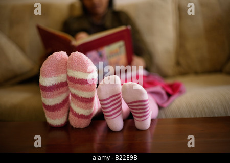 Indian mother 30s and mixed race daughter 4 read a book wearing pink striped socks - Stock-Bilder