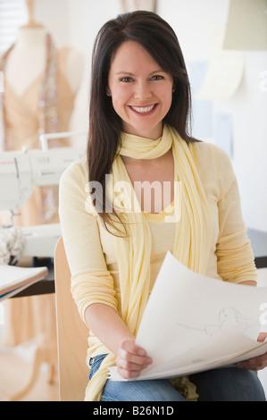 Female clothing designer holding drawings - Stock-Bilder