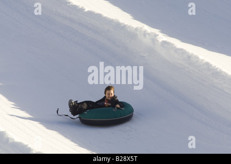 Young boy enjoys a tube ride Whistler British Columbia Canada - Stock Image