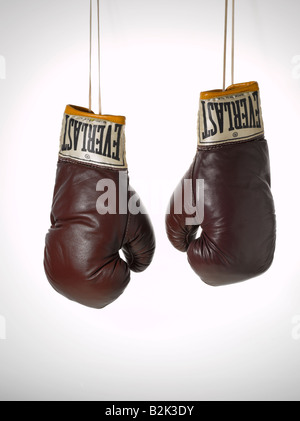 pair of brown vintage brown leather Everlast boxing gloves hanging with strings - Stock Image
