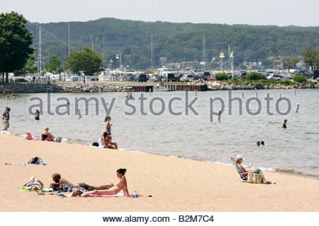 Michigan Traverse City West Arm Grand Traverse Bay Clinch Park beach sunbathe tan swim leisure recreation women - Stock Image