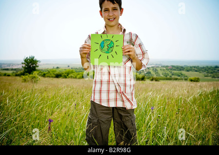 Boy holding picture of earth - Stock Image