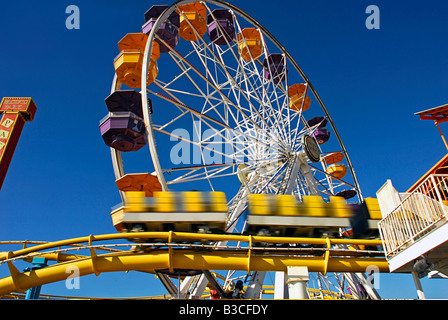 Pacific Park, Santa Monica CA pier family amusement park large Ferris wheel Roller Coaster moving ovber the ocean - Stock Image