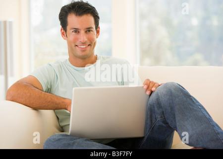 Man in living room using laptop smiling - Stock-Bilder