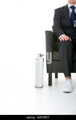 Businessman Sitting Wearing Sneakers - Stock Image