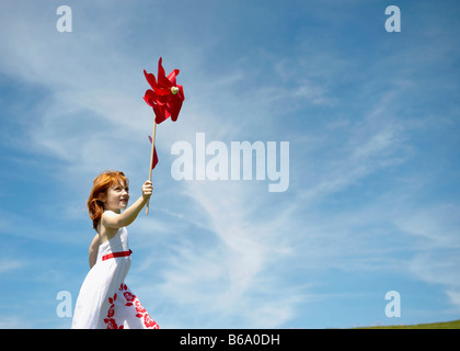 Young girl running with windmill - Stock Image