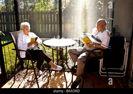 Two retirees reading on a sunny day in a screened enclosure in Florida - Stock Image