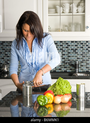 Young woman opening a can of food in the kitchen - Stock Image