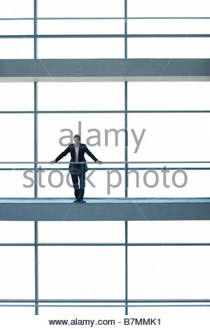 A businessman standing on a walkway in large modern office building - Stock-Bilder