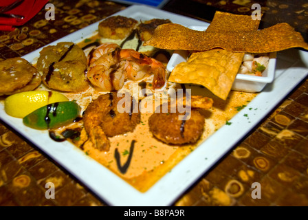 Seafood plate of shrimp breaded and broiled with various sauces white plate food detail San Antonio Texas tx Dining - Stock Image