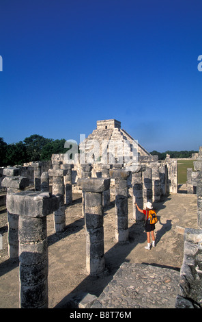 Chichen Itza maya ruins yucatanMexico Group of a Thousand Columns woman tourist wearing red shirt alone castle pyramid - Stock Image