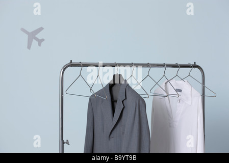 Man's formal and casual outfits hanging on clothes rack, airplane shape in background - Stock Image