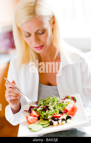 Portrait of mature woman eating salad - Stock Image