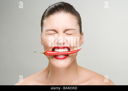 Woman with a red chili pepper in her mouth - Stock Image