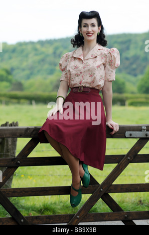 Woman in old fashioned clothing sitting on gate - Stock-Bilder