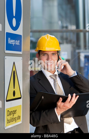 A male manager on a construction site wearing a hard hat and talking on his phone - Stock Image