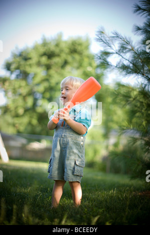 Toddler playing outdoors with a baseball bat - Stock Image